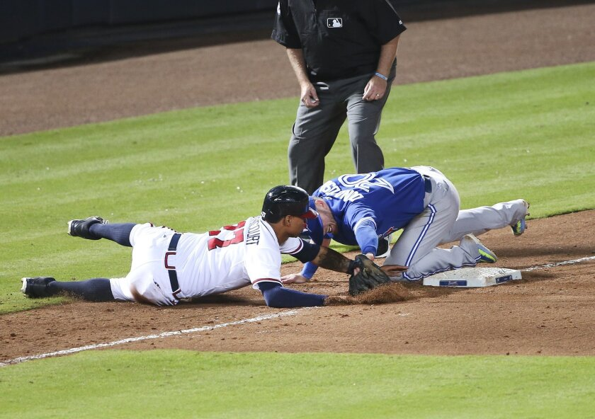 Atlanta Braves' Christian Bethancourt (27) is tagged out at third base by Toronto Blue Jays third baseman Josh Donaldson (20) as he tries to advance on Nick Markakis fly ball in the sixth inning of a baseball game Wednesday, Sept. 16, 2015, in Atlanta. (AP Photo/John Bazemore)