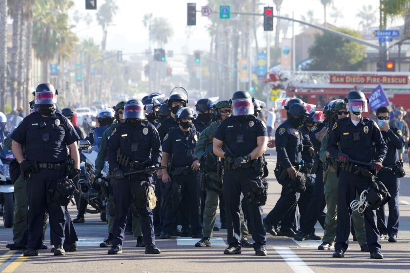 On Jan. 9, 2021, San Diego police officers line up on Mission Boulevard, mostly facing anti-Trump demonstrators