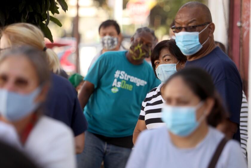 People in masks wait in line
