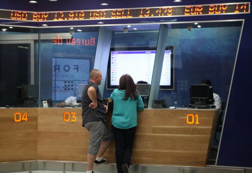 A man and woman stand below a ticker at the counter of a foreign currency exchange bureau at Johannesburg's OR Tambo International Airport Monday, Aug. 24, 2015. An economist says prospects of rising interest rates in the United States, coupled with a downturn in the Chinese economy contributed to the South African currency's record poor performance. (AP Photo/Denis Farrell)
