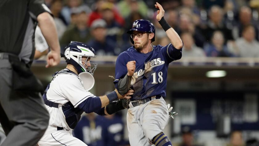Milwaukee Brewers' Eric Sogard is tagged out by San Diego Padres catcher Austin Hedges trying to sco