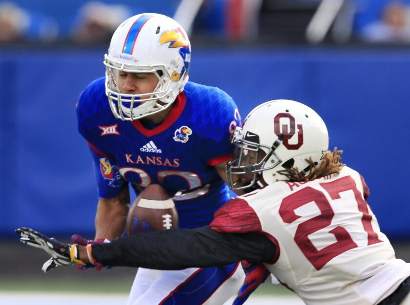 Oklahoma cornerback Dakota Austin (27) breaks up a pass intended for Kansas running back Ke'aun Kinner (22) during the first half of an NCAA college football game in Lawrence, Kan., Saturday, Oct. 31, 2015. (AP Photo/Orlin Wagner)