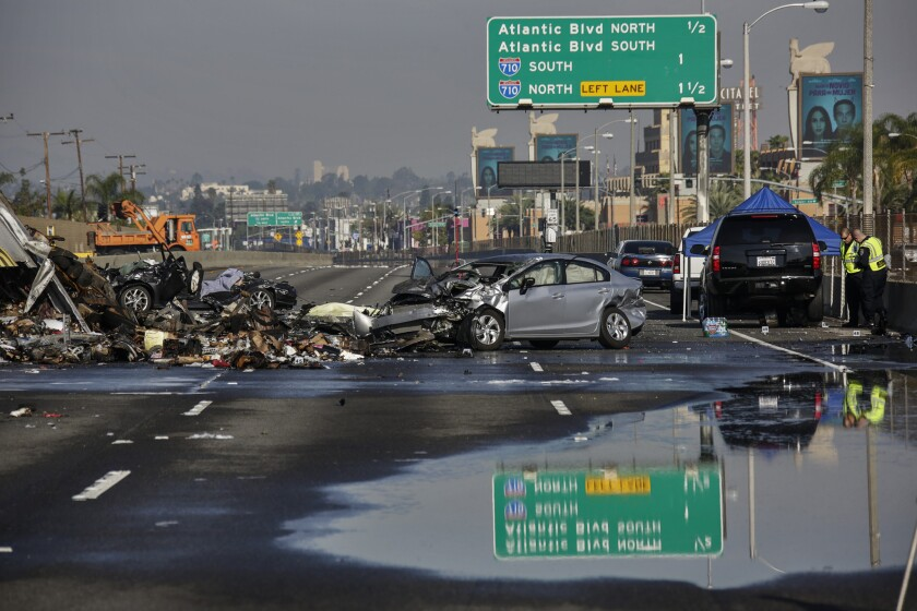 Debris is strewn across the 5 Freeway in Commerce after three people were killed in a fiery multivehicle crash. A motorist who told authorities that he had been racing was charged Tuesday with second-degree murder.