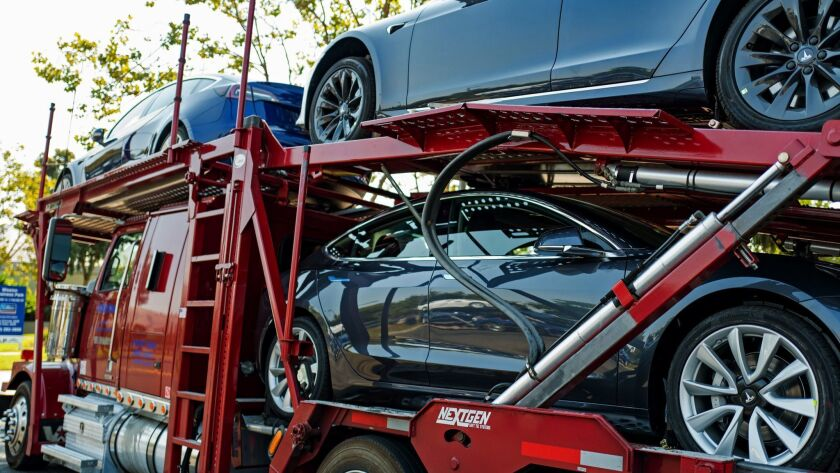 New Tesla cars, including the Model 3, on a car carrier truck awaiting delivery near the company's headquarters and factory in Fremont, Calif.