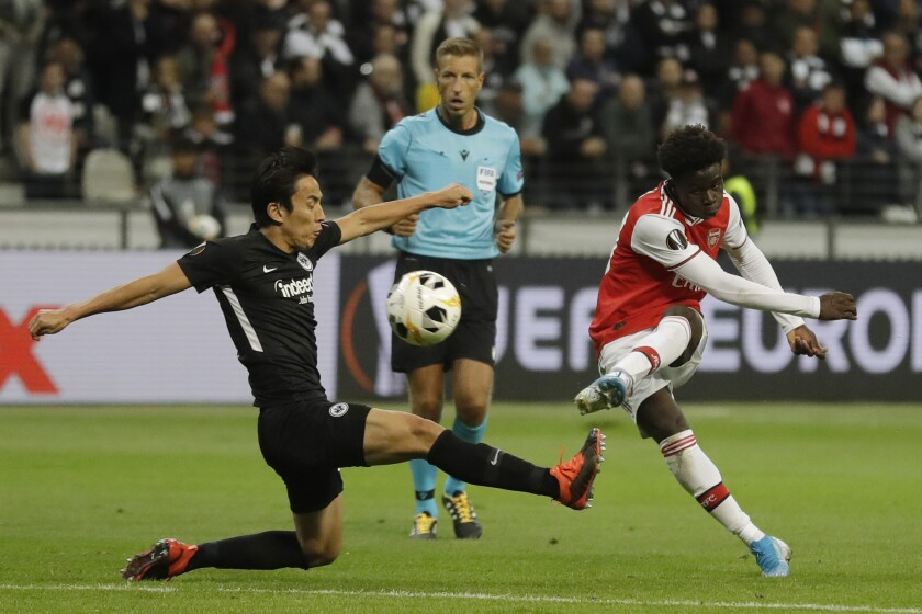 Arsenal's Bukayo Saka, right, scores his side's second goal during the Europa League Group F soccer match between Eintracht Frankfurt and Arsenal in the Commerzbank Arena in Frankfurt, Germany, Thursday, Sept. 19, 2019. (AP Photo/Michael Probst)