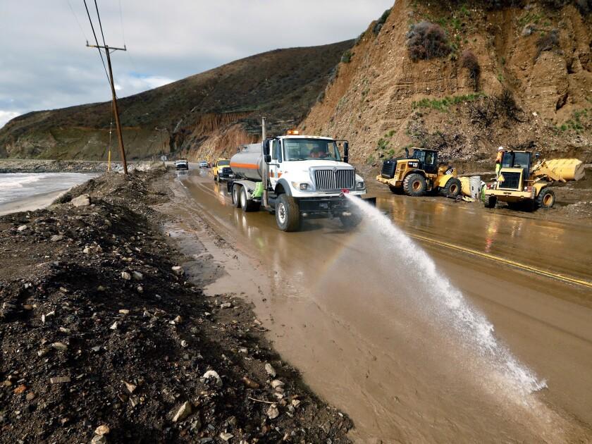 Trabajadores laboran para reabrir un tramo de la autopista de la costa del Pacífico, cerrada debido al lodo, en el condado de Ventura, al oeste de Malibu.