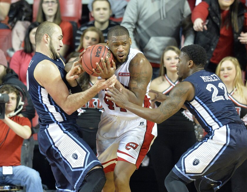 Western Kentucky's George Fant, center, fights to keep the ball away from the defense of Old Dominion's Nik Biberaj, left, and Ambrose Mosley during the first half of their NCAA basketball game, Saturday, Jan. 10, 2015, in Bowling Green, Ky. (AP Photo/Timothy D. Easley)