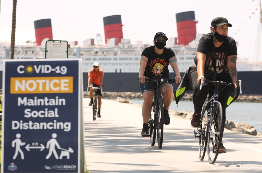Cyclists in Long Beach pedal along a path near the Queen Mary in May 2020.