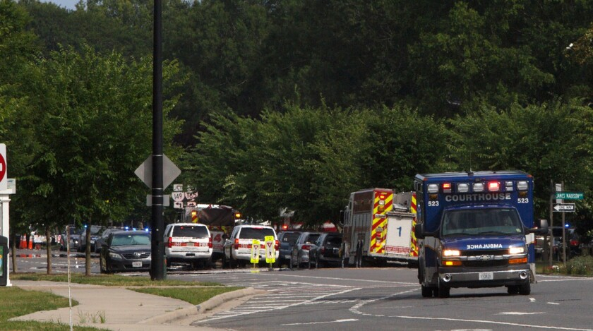 Emergency vehicles are seen near Princess Anne Road and Nimmo Parkway after a shooting Friday at the Virginia Beach Municipal Center in Virginia Beach, Va.