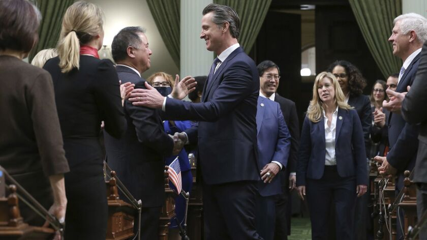 California Gov. Gavin Newsom, center, shakes hands with Assemblyman Phil Ting (D-San Francisco) as he enters the Assembly chambers to deliver his State of the State address in February.