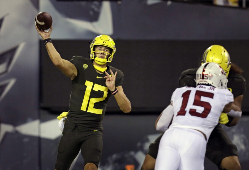 Oregon's Tyler Shough, left, throws downfield against Stanford during the second quarter of an NCAA college football game Saturday, Nov. 7, 2020, in Eugene, Ore. (AP Photo/Chris Pietsch)