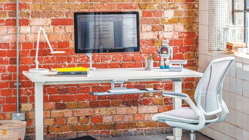 Adjustable LED task lighting and elevating computer stations make working from home more ergonomic. (Humanscale)