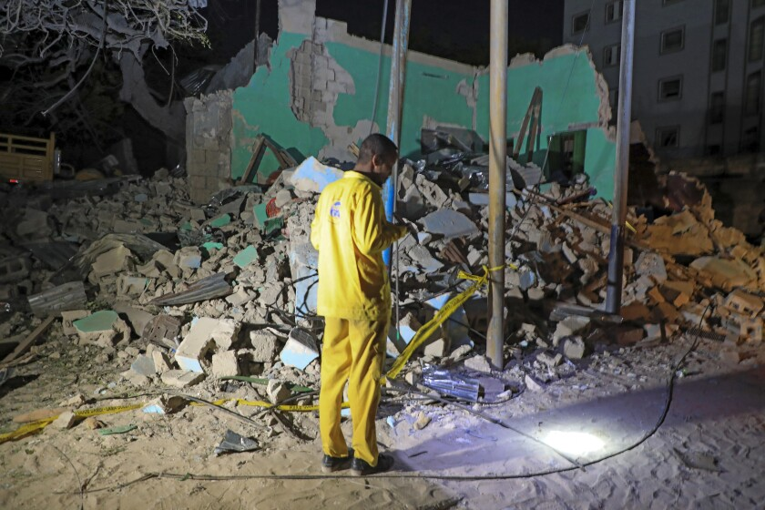 A man observes a destroyed building at the scene of a blast at a popular restaurant in the capital Mogadishu, Somalia Friday, March 5, 2021. A car packed with explosives rammed into a popular restaurant in Somalia's capital on Friday night, and police said at least 10 people were killed and more than 30 wounded. (AP Photo/Farah Abdi Warsameh)