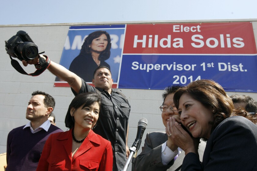 Hilda Solis, right, tries to listen to a cellphone call during a campaign rally on April 5 in El Monte.