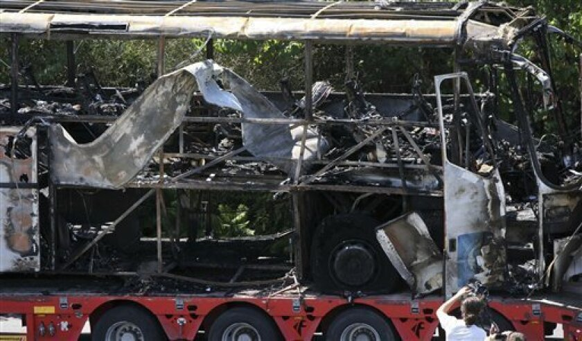FILE - In this Thursday, July 19, 2012 file photo a damaged bus is transported out of Burgas airport, Bulgaria, a day after a deadly suicide attack on a bus full of Israeli vacationers. U.S. officials expect Bulgarian investigators to link the militant group Hezbollah to the July 18 attack in the c
