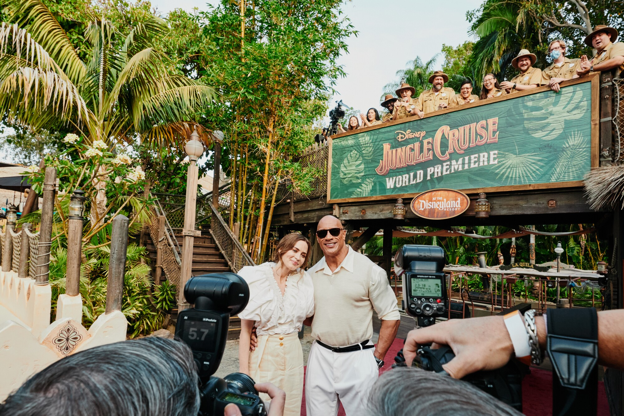 """Photographers take pictures of a woman, left, and man under a """"Jungle Cruise World Premiere"""" sign."""