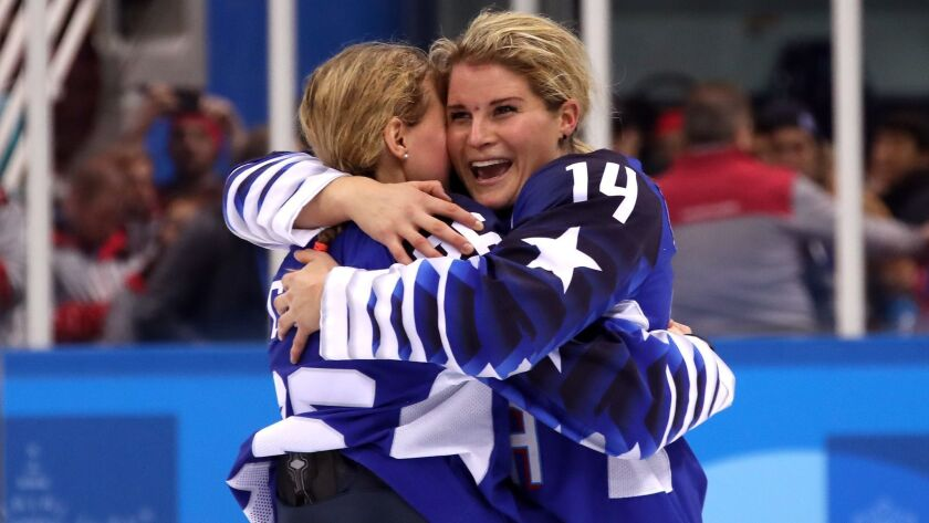 Brianna Decker (14) embraces a teammate after the U.S. defeated Canada in the gold-medal game of the 2018 Winter Olympics.