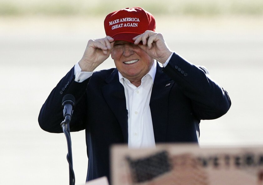 In this June 1, 2016, photo, Republican presidential candidate Donald Trump wears his hat during a rally at the Sacramento International Jet Center in Sacramento, Calif. Trump is suggesting that the Obama administration, for political reasons, plans to keep consumers in the dark about premium incre