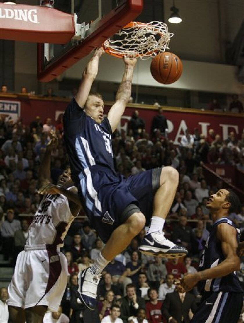 Villanova's Taylor King, top, scores as Saint Joseph's Idris Hilliard (32) attempts to defend in the first half of an NCAA college basketball game Wednesday, Dec. 9, 2009, in Philadelphia. (AP Photo/H. Rumph Jr)