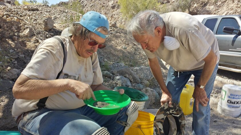 Lee Darling (left) of Southwestern Prospectors and Miners Association points out some gold flakes to retired physician Eric Wetsman, who was learning about mining Saturday during an outing with the group.