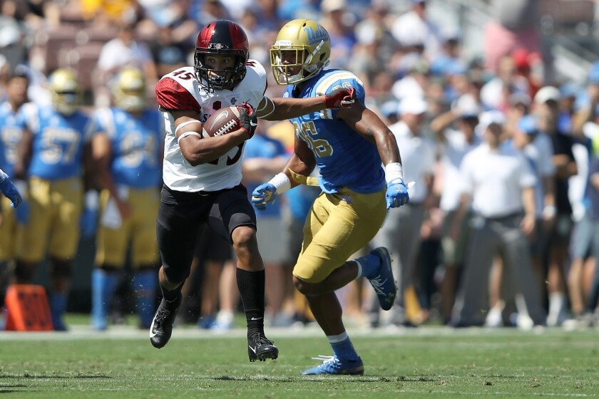 San Diego State redshirt freshman wide receiver Jesse Matthews, a walk-on from Christian High, eludes UCLA's Leni Toailoa during SDSU's Week 2 win at the Rose Bowl.