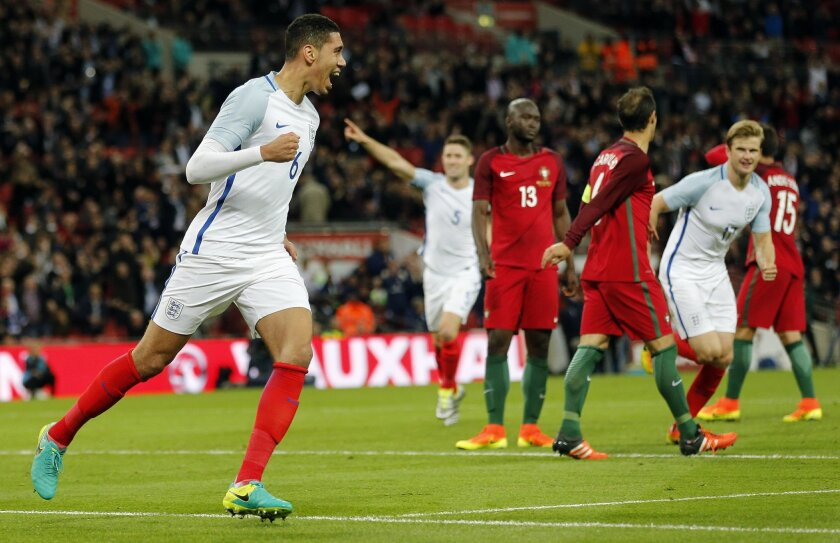 England's Chris Smalling, left, celebrates after scoring during the International friendly soccer match between England and Portugal at Wembley stadium in London, England, Thursday, June 2, 2016 . (AP Photo/Frank Augstein)
