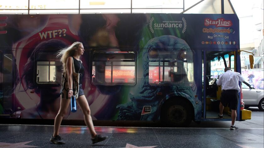 LOS ANGELES, CA-MARCH 19, 2019: A woman walks past a Starline Tours bus on Hollywood Blvd. on March