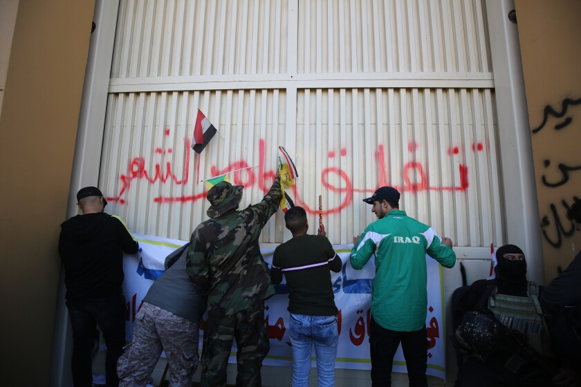 Iraqi protesters hang banners outside the U.S. Embassy in Baghdad after breaching its outer wall Dec. 31.