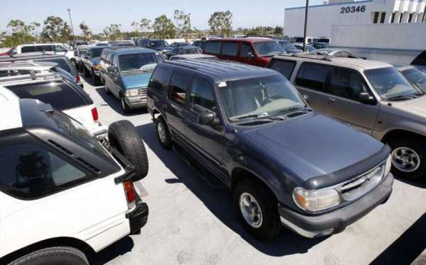 """Older, gas guzzlers are lined up for scrapping as part of the popular """"cash for clunkers"""" program at a lot in Torrance, Calif."""