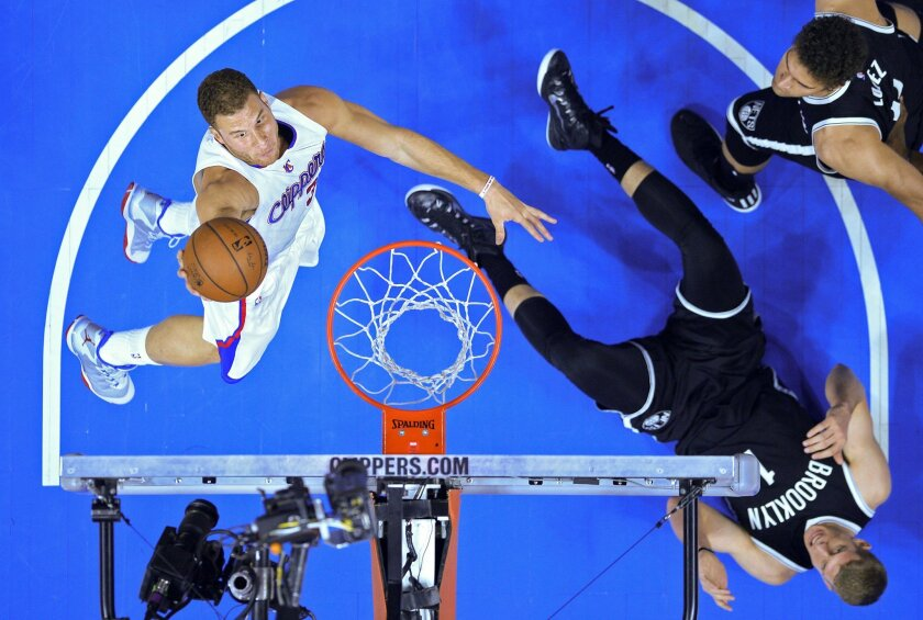 Los Angeles Clippers forward Blake Griffin, left, shoots as Brooklyn Nets center Mason Plumlee falls to the court during the first half of an NBA basketball game, Thursday, Jan. 22, 2015, in Los Angeles. (AP Photo/Mark J. Terrill)