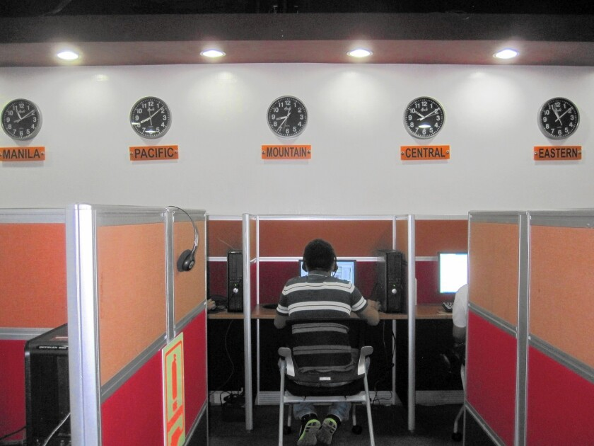 Workers at Visaya Knowledge Process' call center in central Manila sit shoulder to shoulder as they speak with people in the United States. A tote board on one wall tracks in-coming calls as well as metrics like the time spent with each customer.