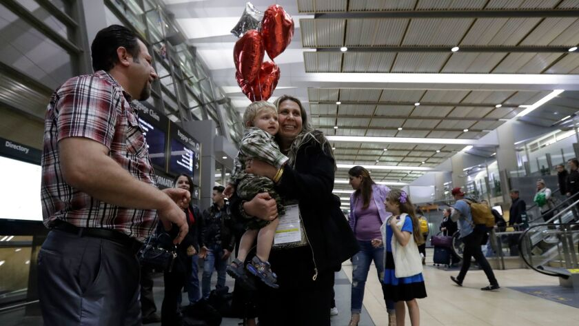 Nadia Hanan Madalo, center, hugs her brother's son at the airport after arriving Wednesday, March 15