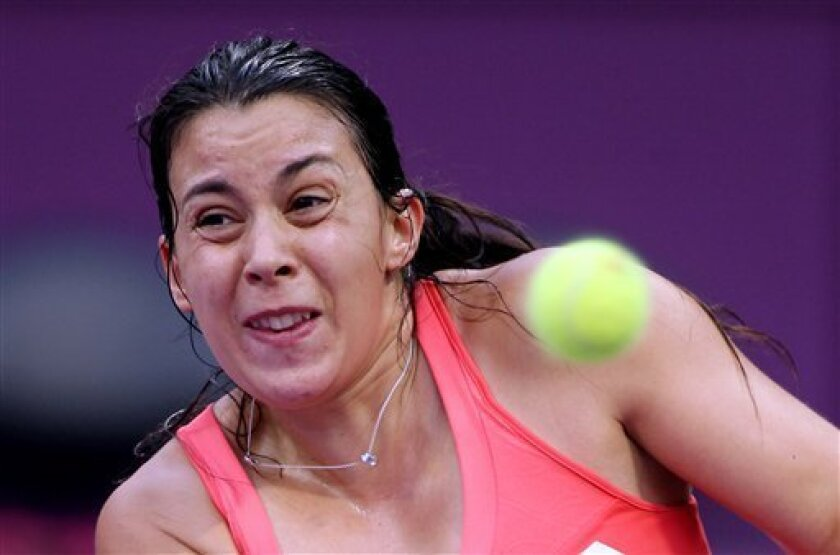 France's Marion Bartoli returns the ball during her match against Francesca Schiavone of Italy on the Second day of the WTA Qatar Ladies Open in Doha, Qatar,Tuesday, Feb. 12, 2013. (AP Photo/Osama Faisal)