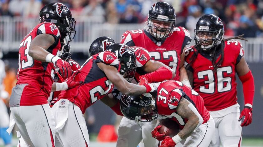 Atlanta Falcons safety Ricardo Allen (37) is mobbed by his teammate after intercepting a pass against the Carolina Panthers during the second half on Sunday.