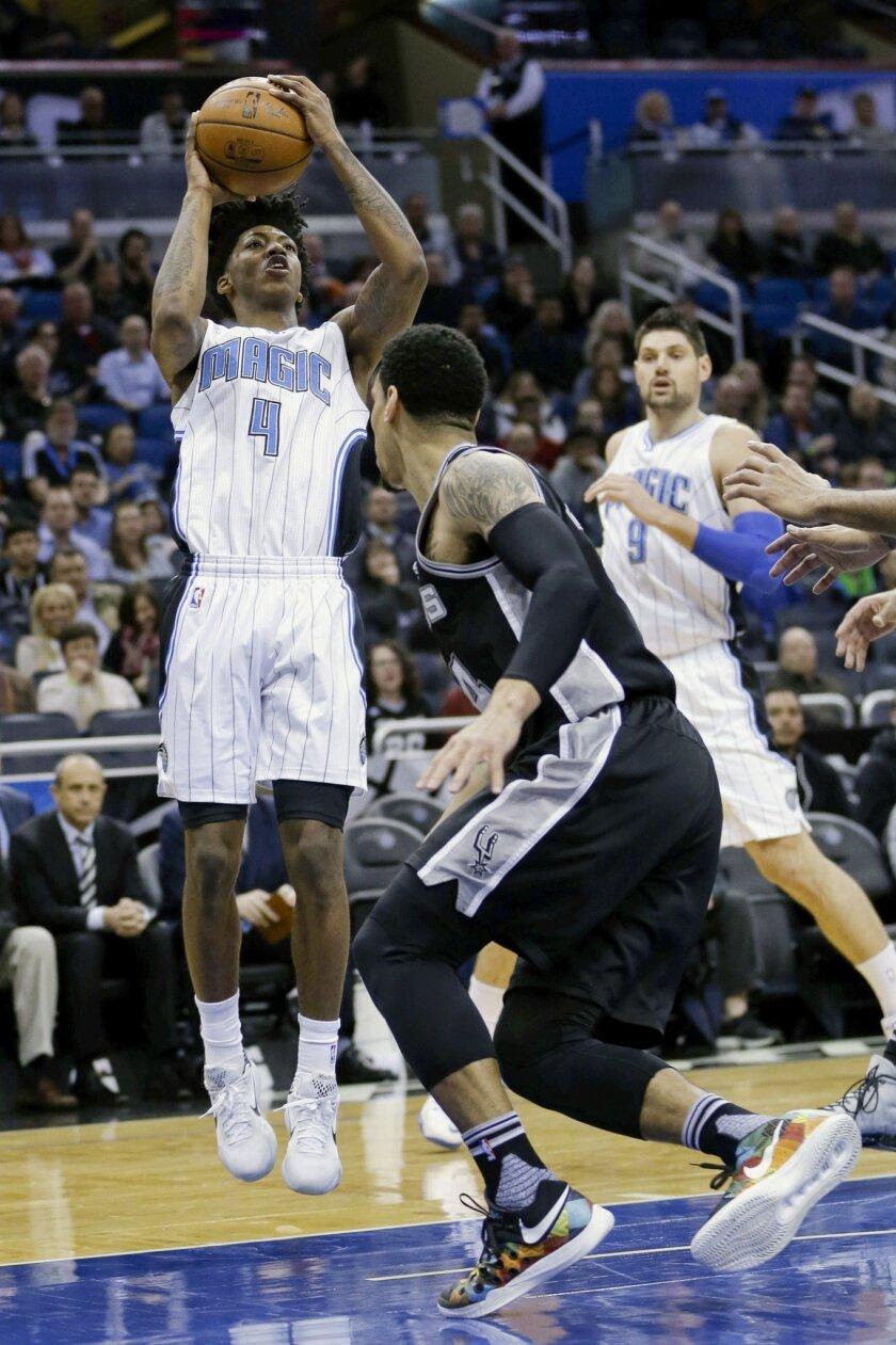 Orlando Magic guard Elfrid Payton (4) shoots over San Antonio Spurs guard Danny Green during the first half of an NBA basketball game, Wednesday, Feb. 10, 2016, in Orlando, Fla. (AP Photo/John Raoux)