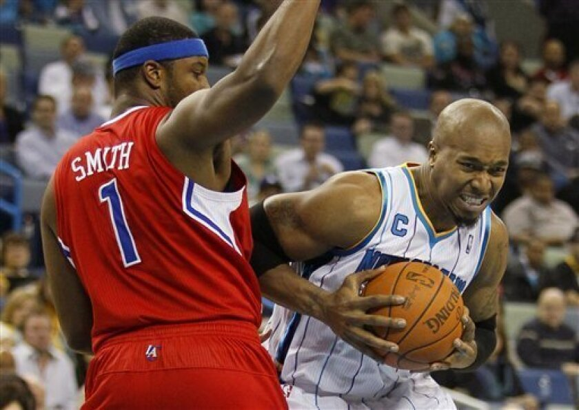 New Orleans Hornets forward David West, right, attempts to drive around Los Angeles Clippers forward Craig Smith in the first half of an NBA basketball game in New Orleans, Tuesday, Nov. 9, 2010. (AP Photo/Patrick Semansky)