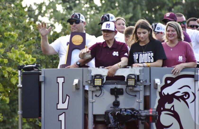 Mississippi State baseball coach Chris Lemonis holds the championship trophy as he, family members and coaches ride in the bucket of a fire truck during a victory parade in Starkville, Miss., Friday, July 2, 2021, honoring the team's win in the College World Series earlier this week. (Chris McMillen/The Starkville Daily News via AP)
