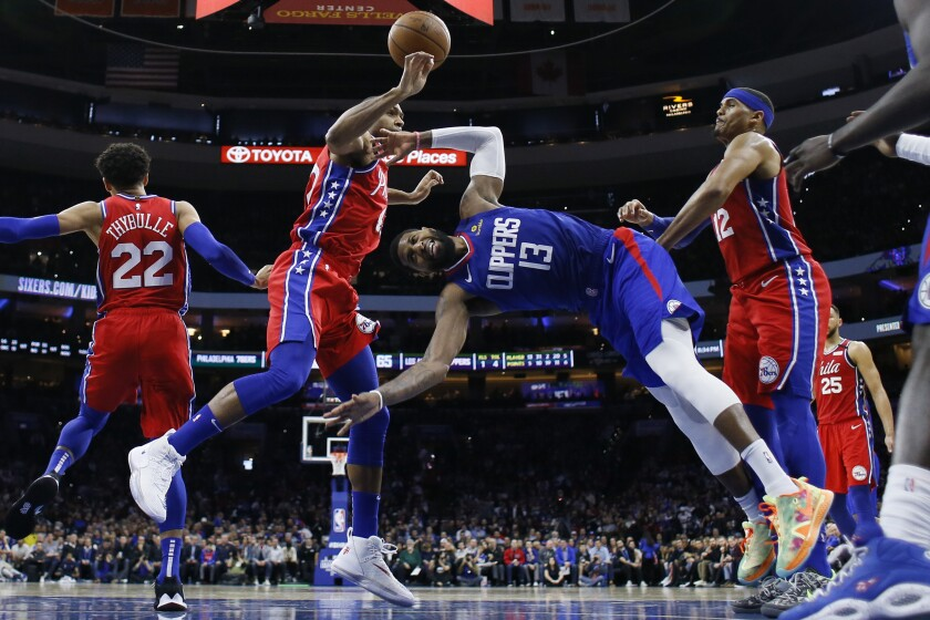 Clippers forward Paul George (13) tumbles to the court after attempting a layup between 76ers center Al Horford, left, and Tobias Harris (12) during a game Feb. 11, 2020, in Philadelphia.