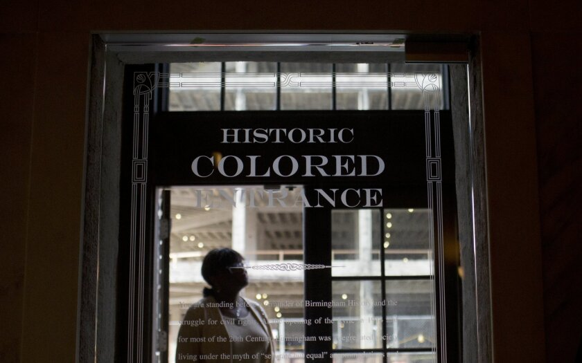 In this Thursday, Jan. 7, 2016 photo, a woman stands in the doorway of then new Historic Colored Entrance at the Lyric Theatre, in Birmingham, Ala. Preservationists had to decide whether to keep reminders of The Lyric's discarded color line before they unveiled an $11 million restoration of the 102