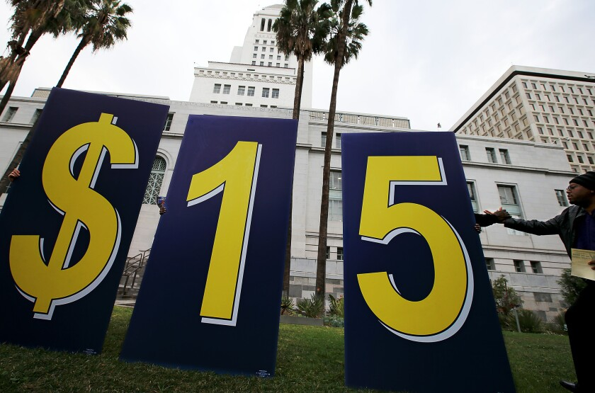 A sign advocating for a $15 minimum wage sits outside L.A. City Hall on Jan. 30 during a rally by workers, businesspeople and civic leaders.