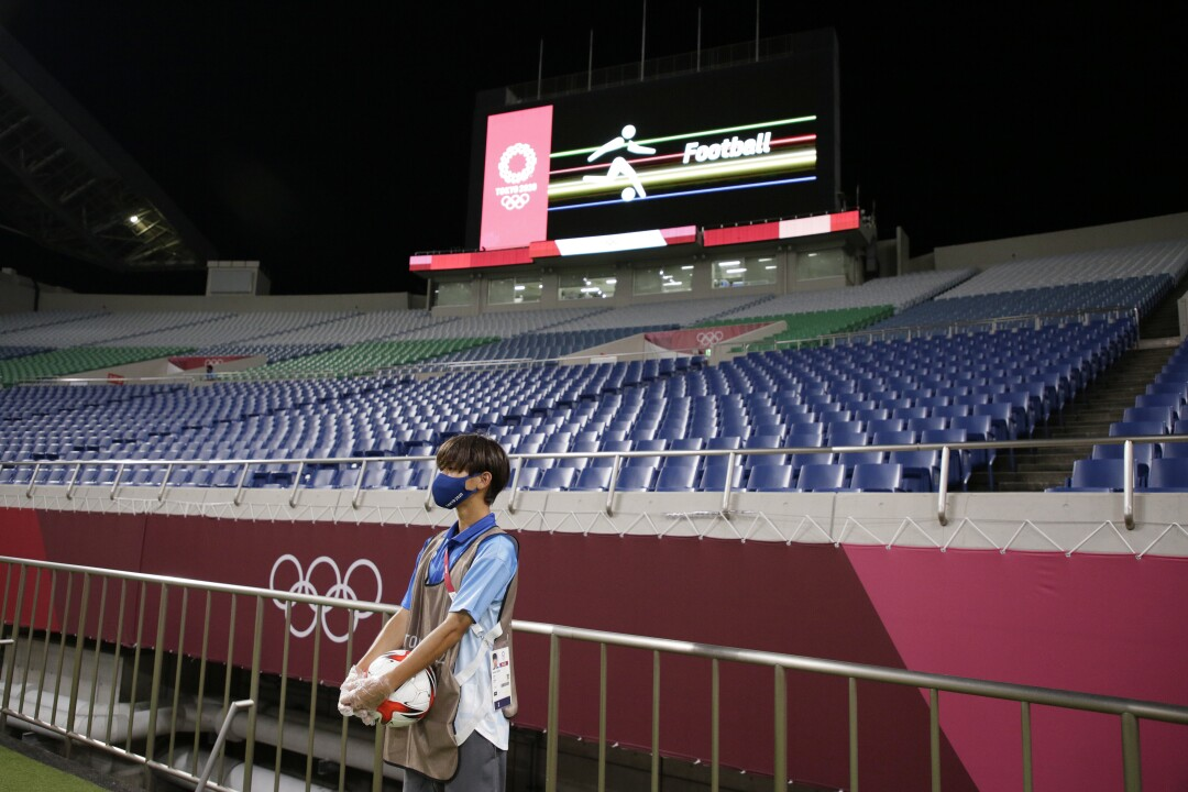 A boy holds a soccer ball. On the wall of the empty stadium behind him are the Olympic rings.