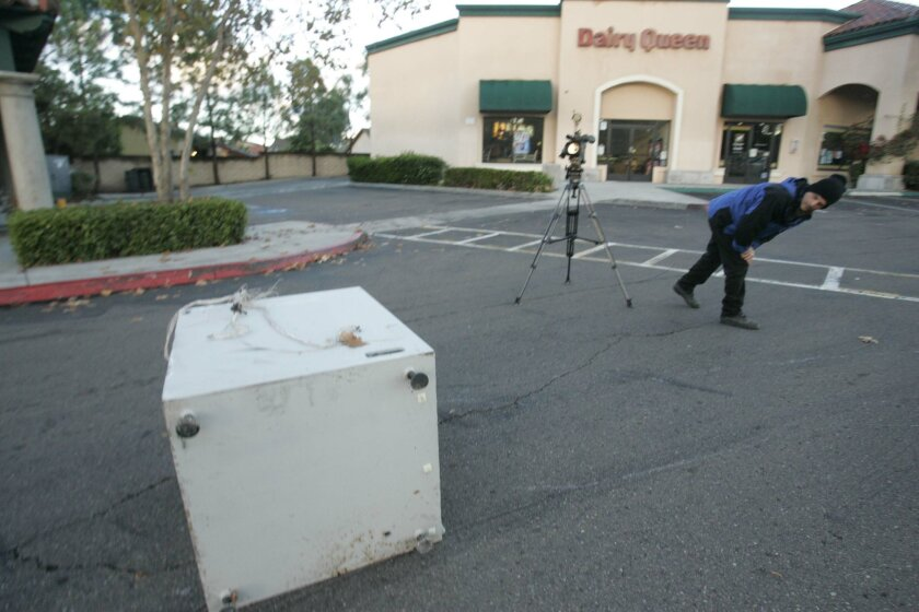 A Channel 8 photographer sizes up the main portion of the machine that was taken, emptied and dumped in the driveway at the shopping center.