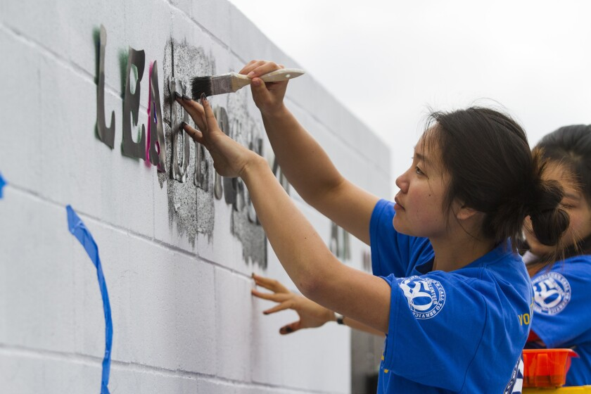 """Jennifer Low, a volunteer taking part in a day of service honoring Dr. Martin Luther King Jr., paints the word """"Leadership"""" onto the handball wall at Oneonta Elementary School in Imperial Beach."""