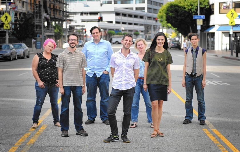 """Artisitc director Yuval Sharon, center, and the """"Hopscotch"""" company stand on a street in downtown Los Angeles."""