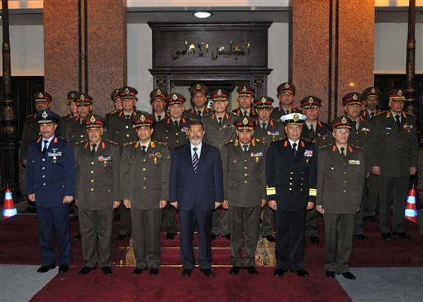 In this Thursday, April 11, 2013 image released by the Egyptian Presidency, Egyptian President Mohammed Morsi, center, poses with military officers after a meeting with the Supreme Council of the Armed Forces in Cairo, Egypt. On Thursday Morsi promoted the heads of Egypt's air force, air defense fo