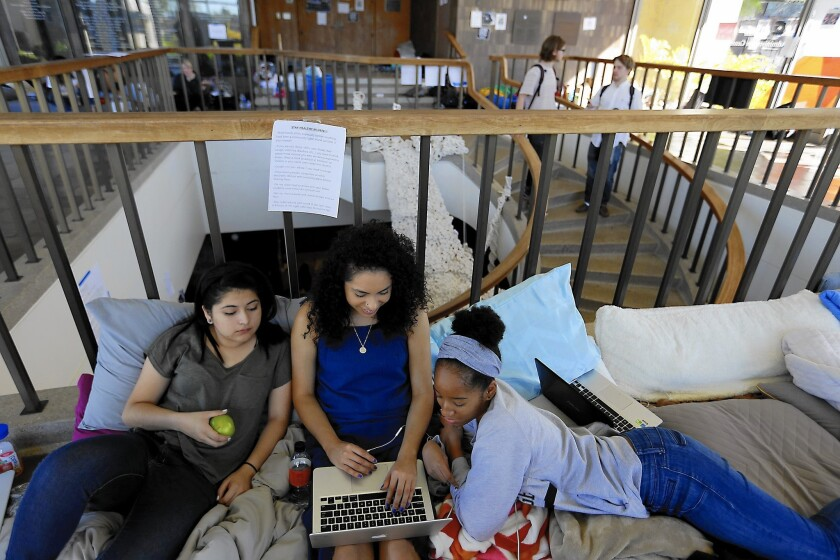Mariel Guido, 18, left, Melissa Morales, 19, middle, and Nasira Pratt, 18, work on homework in the lobby of Occidental College's administration building. Students are occupying Arthur G. Coons Hall to protest the school's handling of diversity issues.