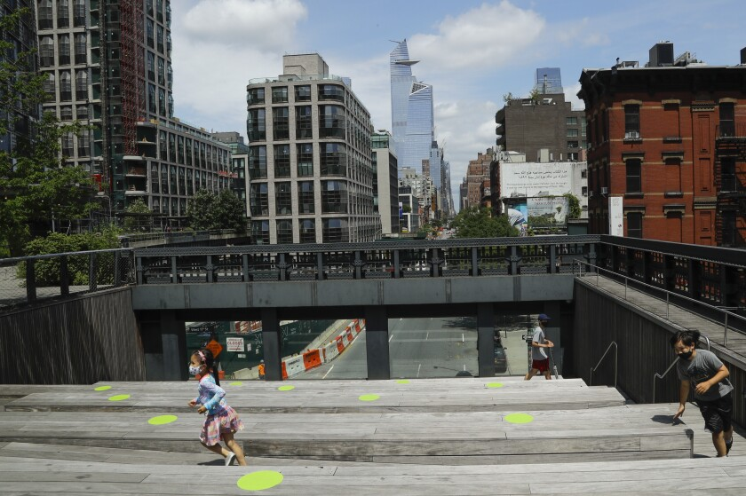 Children wearing protective masks during the coronavirus pandemic play at the High Line Park, Thursday, July 16, 2020, in New York. The High Line opened today after having been closed the last few months during the pandemic. (AP Photo/Frank Franklin II)