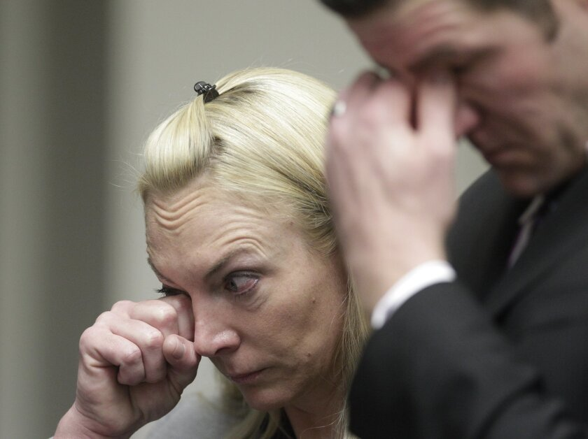 Former San Diego police officers Bryce Charpentier, 32, and Jennifer Charpentier, 42, wipe tears during their sentencing on Friday.