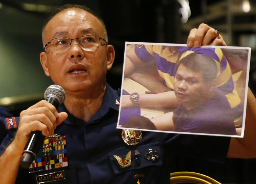 Police Gen. Oscar Albayalde holds an image of the Resorts World Manila attacker, whom he identified as Jessie Carlos at a news conference Sunday in Pasay.