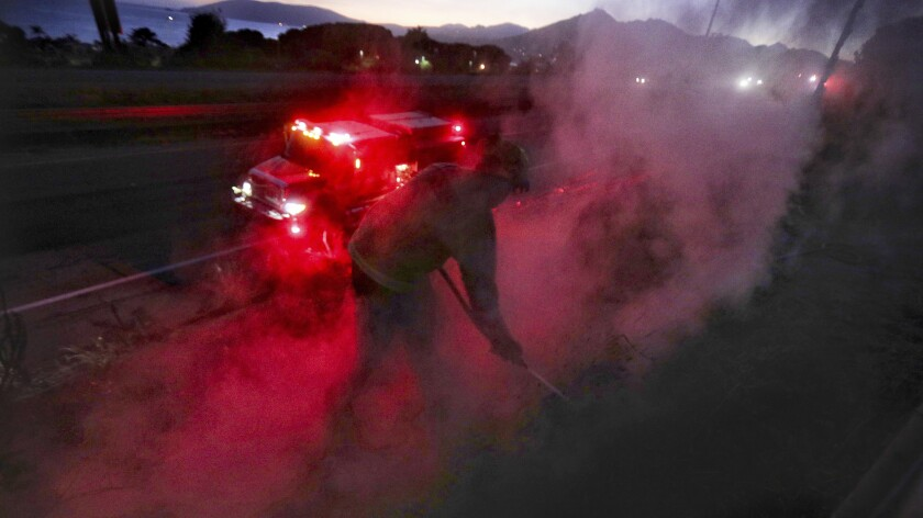 Marcus Anguiano, with the California Department of Forestry and Fire Protection, works on hotspots along U.S. 101 after sunset Monday, June 15, 2020, in Pismo Beach, Calif. A wind-driven brush fire quickly moved south along Highway 101 above Pismo Beach. (David Middlecamp/The Tribune (of San Luis Obispo) via AP)